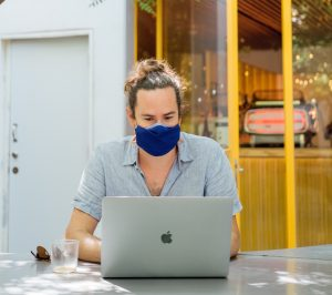 Man in a mask working on a macbook